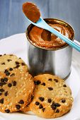 foto of condensation  - Can of boiled condensed milk with spoon and cookies in plate on color wooden table background - JPG