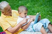 stock photo of grandfather  - grandfather and child using tablet computer in park - JPG