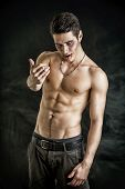 pic of shirtless  - Portrait of a Young Vampire Man Shirtless Showing his Torso Chest and Abs Gesturing to Camera Looking at the Camera on Dark Background - JPG