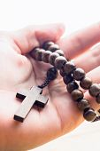picture of rosary  - Hand holding wooden rosary beads in close up - JPG