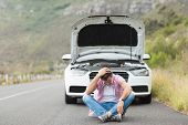 picture of nervous breakdown  - Stressed man sitting after a car breakdown at the side of the road - JPG