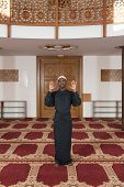pic of muslim man  - African Muslim Man Making Traditional Prayer To God While Wearing A Traditional Cap Dishdasha - JPG