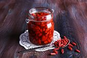 foto of doilies  - Goji berries in glass bottle on lace doily with silver spoon on rustic wooden table background - JPG