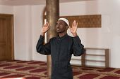 foto of muslim man  - African Muslim Man Making Traditional Prayer To God While Wearing A Traditional Cap Dishdasha  - JPG