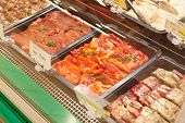 stock photo of marinade  - Meats in marinade on supermarket display - JPG