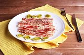 foto of bacon strips  - Strips of bacon with slices shallot in white plate with napkin on wooden table background - JPG