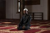 image of muslim man  - African Muslim Man Making Traditional Prayer To God While Wearing A Traditional Cap Dishdasha - JPG