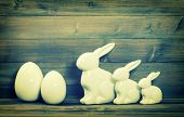 picture of easter eggs bunny  - Easter bunny family and white eggs over rustic wooden background - JPG