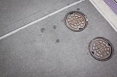 stock photo of manhole  - Two round cast iron manhole cover plates with the word Water on them over the openings on a sidewalk to water supply - JPG