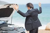 picture of anger  - Anger businessman looking at engine of his car - JPG