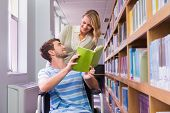 stock photo of classmates  - Smiling disabled student with classmate in library at the university - JPG