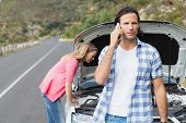 stock photo of breakdown  - Young couple after a car breakdown at the side of the road - JPG
