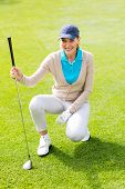 picture of knee-cap  - Female golfer kneeing on the putting green on a sunny day at the golf course - JPG