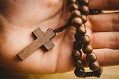 pic of rosary  - Hand holding wooden rosary beads in close up - JPG