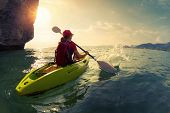 pic of cliffs  - Young lady paddling the kayak near the cliff at sunset - JPG