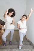 pic of ten years old  - Happy ten year old twin sisters using tablet pc and smart phone - JPG