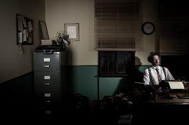 stock photo of 1950s style  - 1950s style reporter working late at night sitting at his desk - JPG