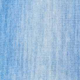 stock photo of denim wear  - Jeans denim light blue cloth fragment as a background texture composition - JPG