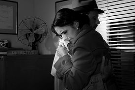 picture of office romance  - Detective consoling and hugging a young woman in his office film noir scene - JPG