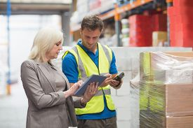 pic of warehouse  - Manager using tablet while worker scanning package in warehouse - JPG