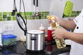 stock photo of chef cap  - Chef open cap of vegetable oil bottle before cooking - JPG