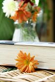 book on a table with flowers