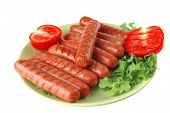 grilled sausages served on green dish with salad and tomato