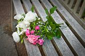 bunch of roses lying on a park bench