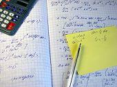 Mathematical formulas, printed calculation, a calculator and a pen