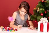 Little girl writing wishlist on red background