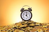 Alarm clock and coins on yellow background