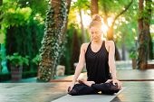 Concentrated Girl Sitting In Lotus Pose And Meditating Or Praying. Young Woman Practicing Yoga Alone poster