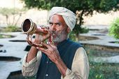 GWALIOR, INDIA -17 FEBRUARY: Old Indian man with turban blowing a trumpet in front of Gwalior Fort complex, February 17, 2008. Gwalior, Madhya Pradesh, India