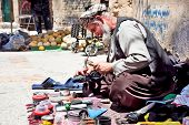 SHIRAZ, IRAN - 27 APRIL: Shoemaker repairing old shoe in his street workshop shown in Shiraz, Iran o