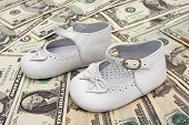 stock photo of mary jane  - White Baby booties on a paper money - JPG