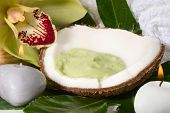 Avocado coconut scrub in coconut shell, orchid flower (Cymbidium sp.) and candles. Suited for relaxi
