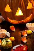 Scatter Halloween candies and orange pumpkin with light