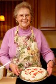 Happy senior woman displaying her no-bake cherry pie.