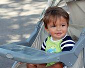 An eighteen-month boy enjoying a summertime stroller ride.