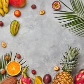 Various juicy exotic fruits, coconut, lychee, carom, pineapple and palm leaves on a gray concrete ba poster