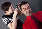 Woman examining man's hair with magnifying glass