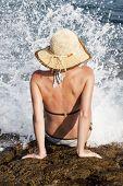 Постер, плакат: женщина с шляпу загорая на скалах вблизи большие волны