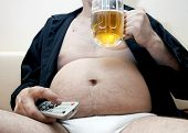 stock photo of beer-belly  - Overweight man sitting on the couch with a beer glass and remote control - JPG