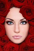 Close-up shot of young beautiful woman face with red roses around