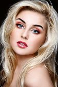 Portrait pf young beautiful girl with curly blond hair and stylish sparkly coral make-up