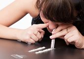 image of crack cocaine  - a girl is sniffing cocaine  - JPG