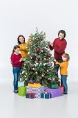 Happy Family Decorating Christmas Tree With Presents Isolated On White poster