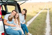 Beautiful Young Family Spending Time Together In Field While Having Car Trip poster