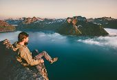 Man Tourist Sitting Alone On The Edge Cliff  Mountains Above Sea Travel Adventure Lifestyle Extreme  poster