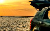 Black Compact Suv Car With Sport And Modern Design Parked On Concrete Road By The Sea At Sunset. Env poster